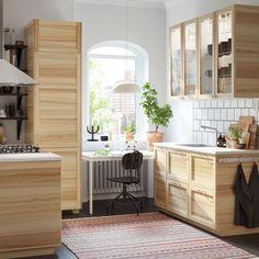 Vitt kök med traditionell naturlig ask och vitrinskåp.