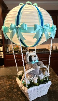 2018 - Created by Ela for a baby shower. Painted basket and wooden dowels, handmade double bows, light teal ribbon with contrasting shiny trim.