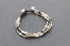 This hand woven bracelet made with dark brown waxed cord weaved together with fancy tiger eyes and white turquoise stone and silver plated beads .