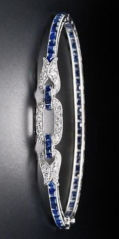 French Art Deco Sapphire and Diamond Bangle Bracelet, A rare, wonderful and exceptionally fine platinum, sapphire and diamond Art Deco jewel from 1920s France. A slender row of vibrant royal-blue rectangular-cut sapphires culminate in a sparkling diamond-set oval link flanked by a pair of sizzling diamond-set flames in this truly exquisite and extraordinary hinged bangle bracelet. The tiny, circular, decorative supports are referred to as chenier tubes. French eagle hallmark on clasp tongue.