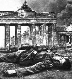 """The famous picture of the body dead German Obertruppführer SS against the Brandenburg Gate. Often used as a symbol and an illustration inglorious end of Nazi Germany. The soldier was shot elsewhere and a image of his body was inserted into this photograph by photomontage. ie Long before """"Photoshop""""."""