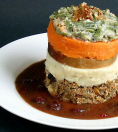 The Leaning Tower of Thanksgiving: stacked layers of Thanksgiving leftovers surrounded it with cranberry-port sauce.