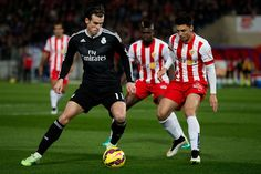 Gareth Bale (L) of Real Madrid CF competes for the ball with Joaquin Navarro JImenez (R) of Almeria UD during the La Liga match between UD Almeria and Real Madrid CF at Juegos del Mediterraneo stadium on December 12, 2014 in Almeria, Spain.