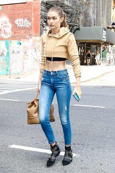 Gigi Hadid sudadera cropped con capucha, de Danielle Guizio; vaqueros azules, botines con tachuelas, de Isabel Marant y bolso de asa corta de cuero marrón con ribetes en naranja, de Versace.