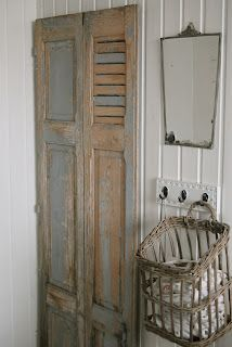These are bi-fold shutters covering a pantry. So Cool!! Also love the basket, hooks and mirror.