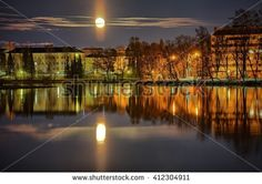 Stock Photo: Cityscape in Finland at moonlit night. Reflections of citylights on the still water of the lake and the moon on the sky.