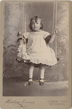 Antique cabinet card photo of a little girl on a swing with her doll circa 1900.