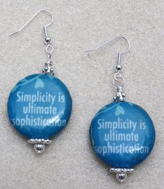"Handcrafted by Teal Palmetto, LLC. Show the world you believe that ""Simplicity is ultimate sophistication"" with these unique earrings.  The two-tone blue decoupage focal beads are coupled with silver-tone accent beads.  The pair has silver-tone fish hook ear wires.  Price: $12"