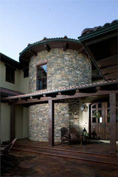 Tuscan house plan with stone turret and stucco facade.