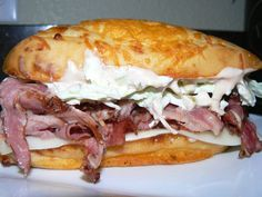 Hot Pastrami, Swiss Cheese, Creamy Cole Slaw, and House Russian Dressing on a Grilled Onion Cheese Roll
