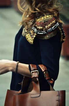 Black blouse with multicolored shoulder decorations.
