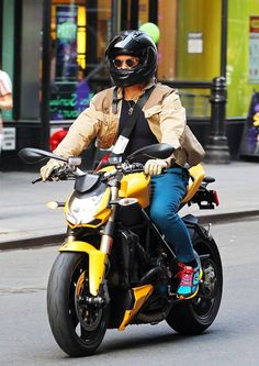 Actor Orlando Bloom was spotting riding down a New York City street on a yellow 2012 Ducati Streetfighter 848 bike. He wearing a pair of Oliver Peoples Sheldrake Sunglasses with a tan jacket, turquoise pants, and sneakers