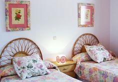 Dormitorio con muebles de mimbre y textiles de flores