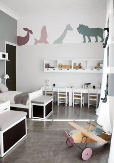 J'aime beaucoup cette chambre d'enfants aux tons blancs-gris et les ombres des animaux peintes aux murs, dans une gamme de couleurs douce et moderne. L'alignement des bureaux et des casiers suspendus est également très réussi.