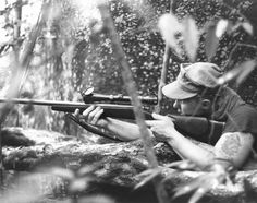 """A Marine sniper takes aim, 1970. A tattoo of a bulldog wearing a helmet with """"sniper"""" inked beneath it is visible on the corporal's upper arm."""