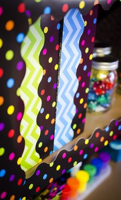 Cover binders or bookshelves with the Multicolor Dots on Black Scalloped Border Trim. Each piece is 35 inches long. 12 pieces per pack. 35 feet of trim per pack.