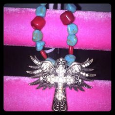 Turquoise large cross necklace Handmade ! Summertime staple . Amazing find at a southern market show . Features turquoise and red stones , with a large crystal cross in the middle that is surrounded by angel wings. Glitzy and glam and definitely a statement piece ! Jewelry Necklaces