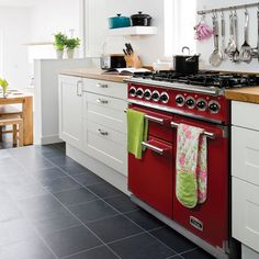 Go Bold! Our range of bright colours can make a stand-out feature within any understated kitchen. Cherry red here creates impact and looks the part against slate flooring.