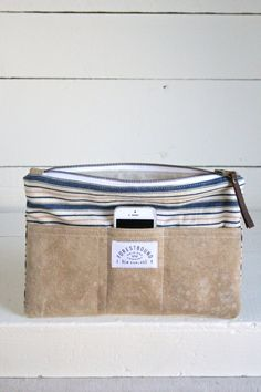 1940's era Ticking Fabric Pocket Utility Pouch $65 Sturdy utility pouch made from blue, beige and salmon striped ticking fabric salvaged from a 1940's era mattress cover. Features three outer pockets made from WWII era US millitary canvas.  Fully lined with beige cotton canvas. Closes with a durable brass zipper and handmade leather pull.   Measures approximately 12 in wide, 9 in tall.  Much time and care is put into making all Forestbound Originals one of a kind.