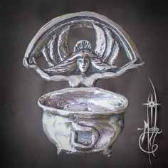 An amulet of The Crone standing before her cauldron, wings and rainbow of manifestation represents Temperance