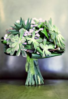 Like that the succulents are the main star of this boquet.  Though ideally it'd be more in the silver/greys with pops of red and less green/purple
