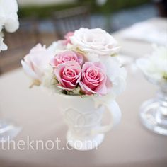 Petite milk glass mugs held arrangements of pink roses in addition to the high and low centerpieces Min and Jason picked to decorate the tables.