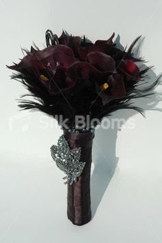 Ultra modern aubergine calla lily bouquet with feathers and pearls. aubergine wedding flowers, handmade to order in any colour. Very realistic, really superb quality with crystal sprays and brooch. Beautiful calla lilies that have all been individually airbrushed. Handle is tied off beautifully in aubergine satin ribbon. Stunning. Finished off with black tendril feathers and pearl wire to the handle. Circumference: 28 inches (approx).