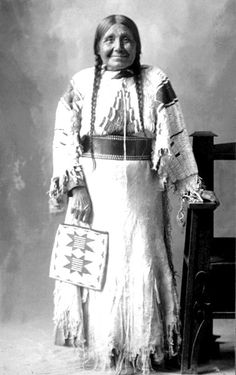 Nez Perce woman (Mrs Red Rock?) in ceremonial regalia poses for a formal portrait displaying a star patterned bag. No date.