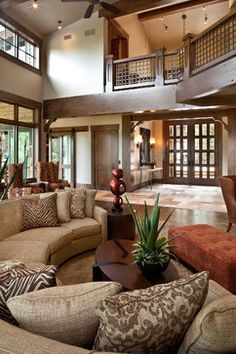 Gorgeous living area with brown wood and brown patterns - love the balcony and rounded couch!