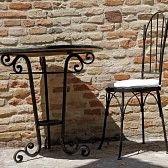 hierro forjado : silla de hierro forjado y una mesa en la terraza soleada, Italia, Europa
