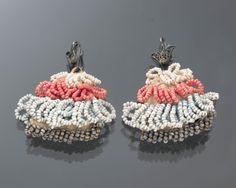Paar borstakertjes met akerhaakjes van ongewaarborgd zilver in filigreintechniek. De akertjes hebben een versiering van kralenwerk in wit, rood, blauw en zilver. De akertjes werden op Marken gedragen aan de punten van de schouderdoekjes. #NoordHolland #Marken