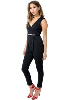 A party-ready jumpsuit featuring a surplice neck and drape hip pockets. Sleeveless. Belt loops at the waist with a metal plated leatherette belt. Tapered pant. Finished leg openings