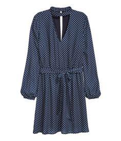 Mørkeblå/Prikket. Kort kjole i vævet kvalitet. Kjolen har lav, opretstående krave og udskåret parti for og bag. Lange ærmer. Knaplukning i nakken. Skåret