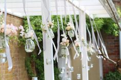 Hanging walkway installation at Northbrook Park located in Surrey. Lace covered glass jars filled with blush Roses, stocks and Sweetpeas. Lace and grey hanging ribbons and glass t-lights. Designed and created by www.hannahberryflowers.co.uk for a wedding at Northbrook Park. #romantic and #blush