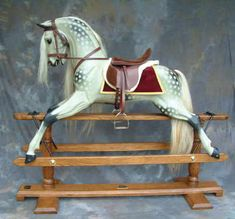 Legends' own rocking horse carving design in a traditional dapple grey finish.    Slightly 'antique' varnish, burgundy saddle blanket with gold trim, burgundy leather tack and light grey mane and tail.    Medium oak stand.  Available on bow or safety stand.