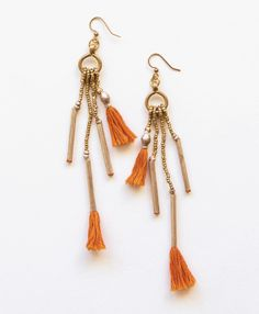 Geometric bar-shaped beads hang down and are accented with pops of bright orange fringe for a feisty feel. #earrings #fringe #orange