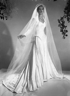1951:  A satin wedding dress by Mercia with a long veil held in position by a tiara. Photo: Chaloner Woods, Getty / Hulton Archive