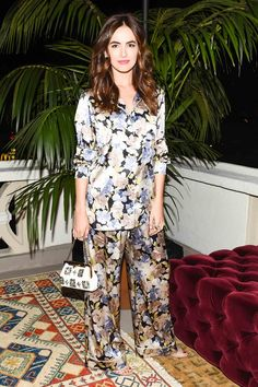 Camilla Belle wears floral silk pajamas, a beaded bag, and nude sandals