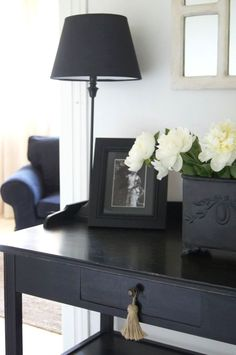 Black furniture and accessories on white walls.
