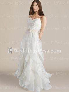 Asymmetrical tiered draping features this informal bridal gown with spaghetti straps.