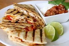 Grilled Chicken Quesadillas    Ingredients:  1 tbsp. chili powder  2 tbsp. fresh cilantro, minced  1 tbsp. olive oil  Juice of 1 lime  1 tsp. salt  1 tsp. cumin  ½ tsp. red pepper flakes  4 boneless, skinless chicken breasts halves  Half a yellow onion, roughly chopped  2 tomatoes, seeded and diced  Corn tortillas (6-7 inches)  Cooking spray  Shredded cheese (pepper jack, cheddar, etc.)