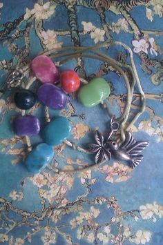 Collar de cuentas de cerámica,montado en cordón verde agua de cola de ratón, con cierre de plata,co un motivo central muy especial, un colibrí color p