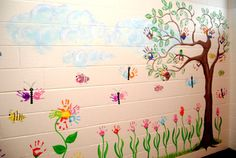 Mural on wall with kids handprints for butterflies, flowers, bees and birds. Clever!