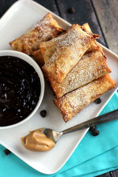 melty peanut butter-chocolate chip cookie dough-stuffed shardy egg rolls w/ dark chocolate dipping sauce & powdered sugar topping