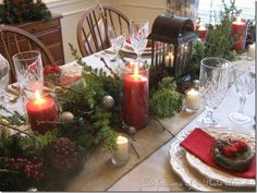 Tablescape with burlap runner, black lantern, greens, red candles