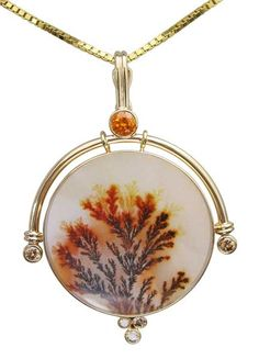 A beautiful dendritic agate framed in gold in this pendant by artist Patrick Murphey.