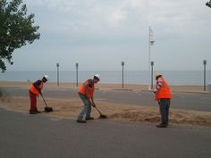 Members of the Summer Youth program clean up a parking lot.
