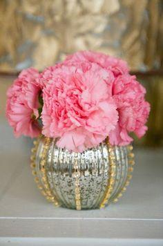 La simplicidad de los claveles fucsias se equilibra perfectamente con este jarrón decorado con detalles dorados y brillos. Los centros de mesa florales más románticos para bodas. Imágenes: Style Me Pretty.