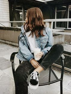 Blue denim jacket over white tee and black jeans.