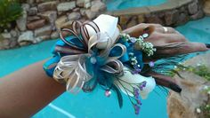Corsage for prom or homecoming that matches teal dress.  1. Start with any corsage base. I used a 4 layer rhinstone braclet that I bought from walmart for $5.00. Use ribbon to tie to the metal corsage base to the bracelet. 2. Hot glue 1 peacock feather and a couple other tan and teal feathersto the metal base.  3. I used teal satin ribbon for the base. Loop the ribbon to cover a majority of the base of the corsage. Tie floral wire around the center to close the ribbon. Now hot glue the…